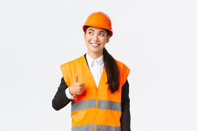 建設工事に満足し、安全ヘルメットと反射ジャケットに立って、左上隅を見て、承認で親指を立てて満足している幸せな笑顔の女性アジア人建築家