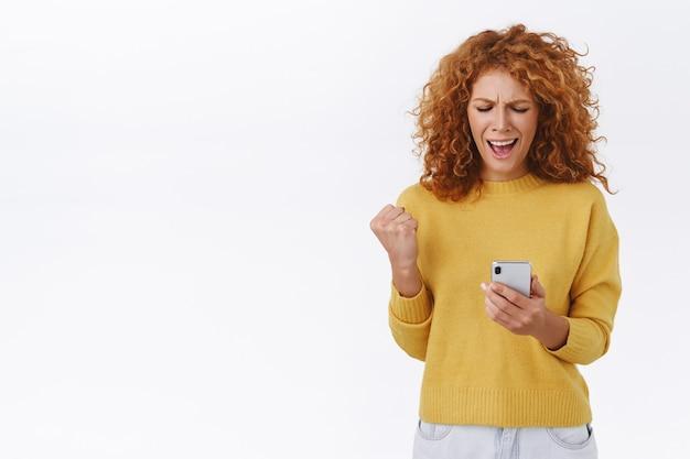 Довольная, счастливая торжествующая рыжая кудрявая женщина, накачивает кулаком и говорит да, сжимает руку, держит смартфон, читает что-то классное, получает бонусы в приложении, уровень победы, белая стена