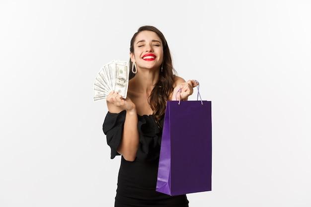 Donna soddisfatta e felice che gode dello shopping, che tiene borsa e denaro, sorridendo compiaciuta, in piedi su sfondo bianco.