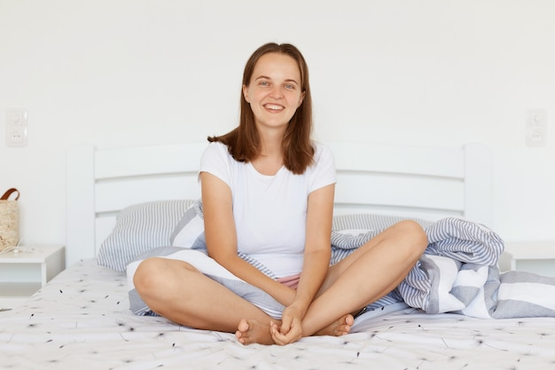 Satisfied happy young adult female wearing white casual t shirt sitting on bed in light room, looking at camera with positive smile, spending weekend morning at home.