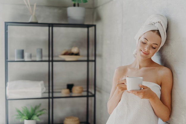 Satisfied healthy european woman poses near wall in bathroom, wrapped in white soft towels, holds mug of tea, being relaxed after spa treatment and taking bath, enjoys hygiene treatments at home