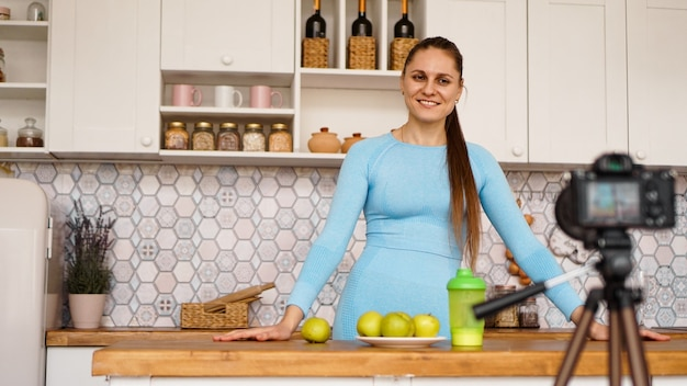 自宅のキッチンに立っている間、健康的な食事についての彼女のビデオブログエピソードを記録している満足した健康な若い女の子。女性はフレンドリーで笑顔です