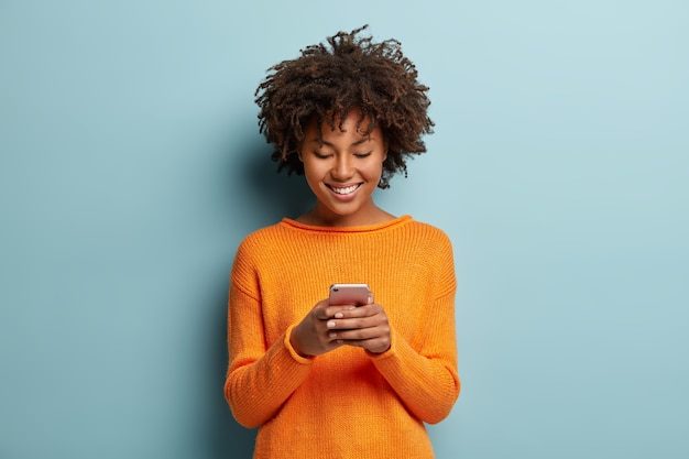 Satisfied hipster girl with afro haircut, types text message on cell phone, enjoys online communication