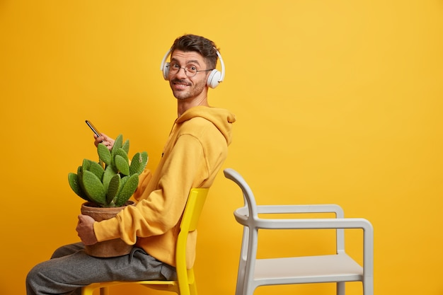 Satisfied hipster guy sits back to empty chair uses mobile phone for surfing internet and messaging listens audio track in wireless headphones dressed in casual sweatshirt carries potted cactus