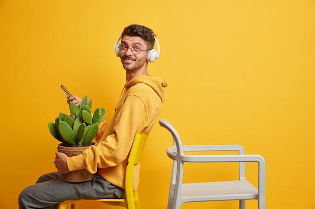 満足している流行に敏感な男が空の椅子に座ってインターネットサーフィンに携帯電話を使用し、メッセージングはカジュアルなスウェットシャツに身を包んだワイヤレスヘッドフォンでオーディオトラックを聞く鉢植えのサボテンを運ぶ