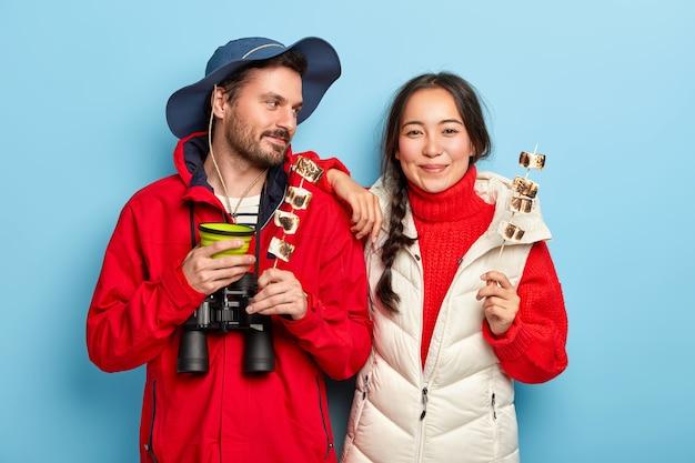 Marito e moglie soddisfatti tengono bastoncini di marshmallow arrosto, fanno un picnic nella foresta, bevono caffè, vestiti con abiti casual, godono del tempo in campeggio isolato su un muro blu