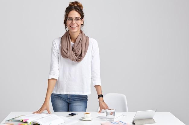 満足しているインテリジェントな女性家庭教師は白いジャンパーとジーンズを着ています