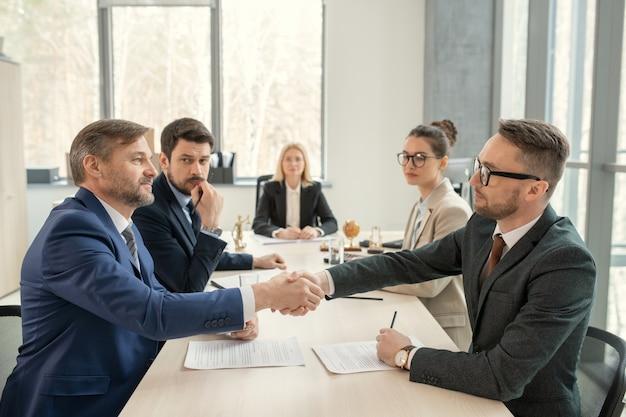 Довольные юристы в костюмах сидят друг напротив друга и пожимают друг другу руки при достижении соглашения о контракте.