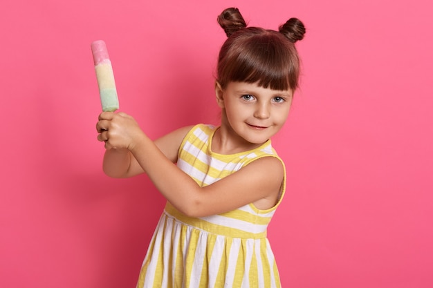 Satisfied little child holding water ice cream with both hands, looks at camera, has two knots, wearing striped summer dress, posing isolated over rosy background.