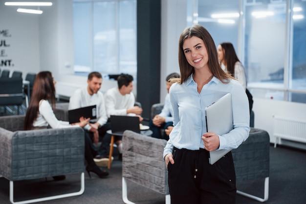 満足そうな表情。バックグラウンドで従業員とオフィスに立っている若い女の子の肖像画