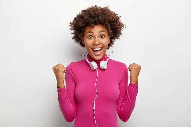 Satisfied lovely dark skinned woman makes hooray gesture, triumps from success