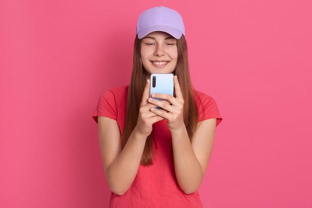 Удовлетворенная милая женщина, держащая современный мобильный телефон, отправляет смс со своей подругой онлайн, одевает красную футболку и бейсболку, позирует на розовой стене, стоя с очаровательной улыбкой.