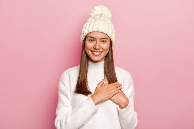 똑바로 머리를 가진 만족스러운 사랑스러운 여자, 남자 친구로부터 따뜻한 말을 받고, 감사하는 몸짓을하고, 편안한 흰색 스웨터와 모자를 쓰고, 분홍색 벽 위에 절연