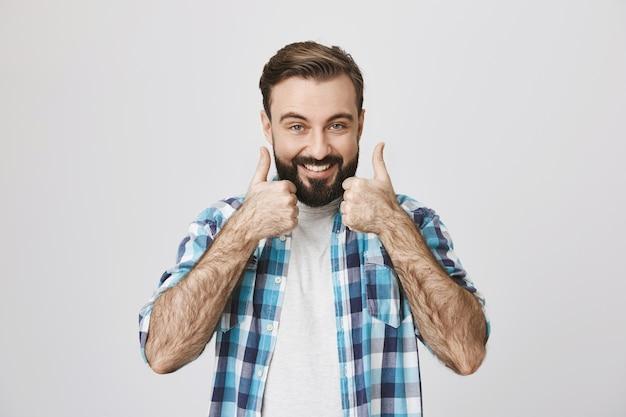 Il cliente maschio soddisfatto mostra i pollici in su e sorride