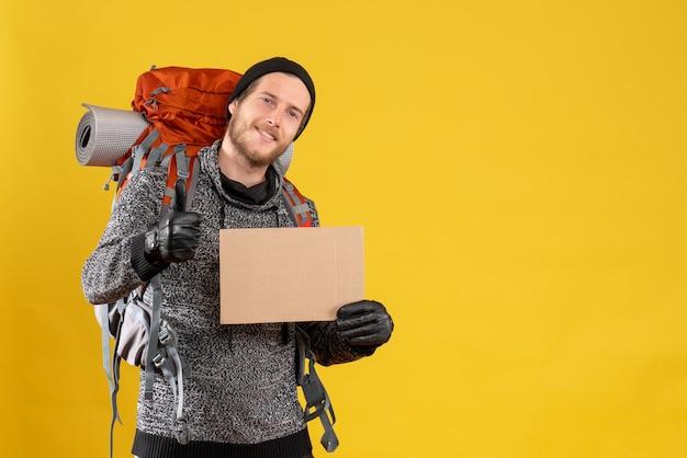 Довольный мужчина-автостопщик с кожаными перчатками и рюкзаком держит пустой картон, показывая пальцем вверх знак