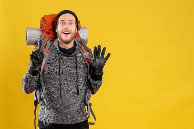 革手袋と手を上げるバックパックで満足した男性のヒッチハイカー