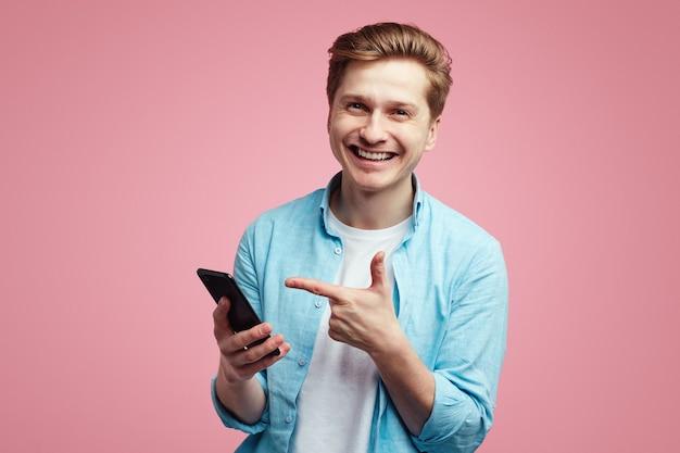 満足している青いシャツを着た男性が、スマートフォンで人差し指を指す