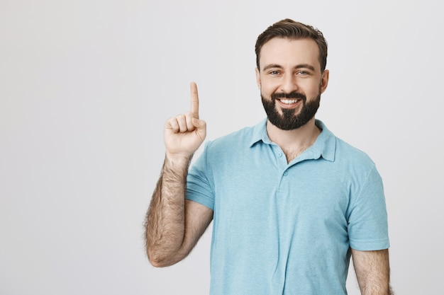 Удовлетворенная мужская модель улыбается, указывая вверх