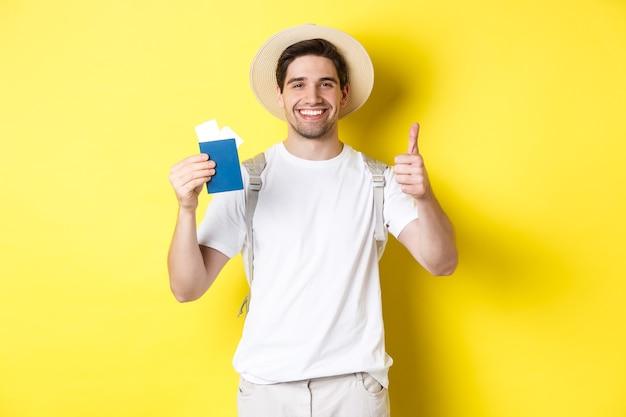 Довольный турист-мужчина показывает паспорт с билетами и показывает большой палец вверх, рекомендует туристическую компанию, стоит у желтой стены
