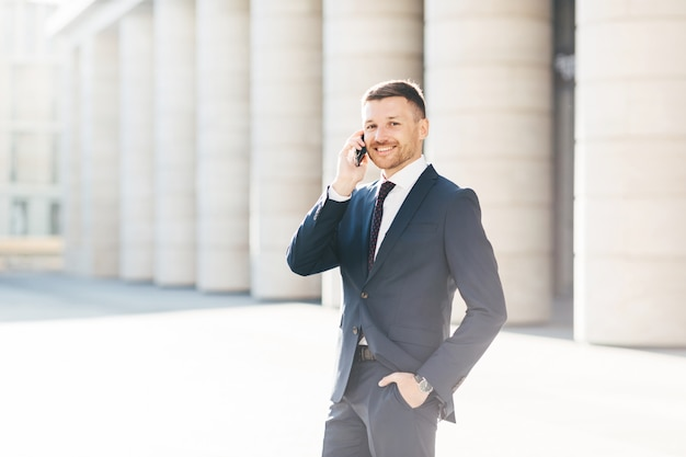 Satisfied male with positive look solves banking problems while calls to operator via smart phone