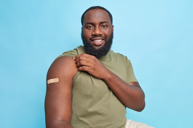 Satisfied man after vaccination shows adhesive bandage on arm got covid 19 vaccination to cure disease isolated over blue wall