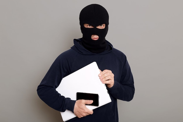 Satisfied man robber steals laptop beech and phone
