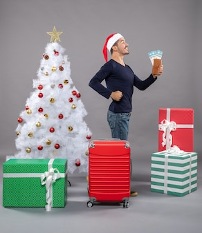 Uomo soddisfatto stand vista laterale tenendo i suoi biglietti di viaggio e mostrando i muscoli del braccio su grigio