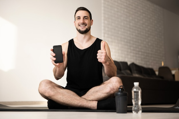 Satisfied man thumbs up and shows favorite sports mobile app. workout everyday concept. two sports water bottle. happy man sits on black yoga mat with crossing legs. smart lifestyle concept.