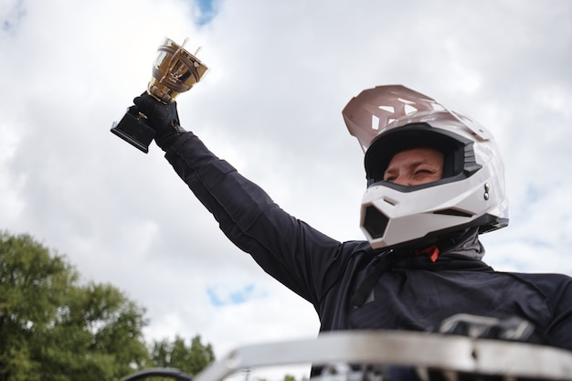 Satisfied man in white helmet raising hand with motorcycle competition cup after winning competition