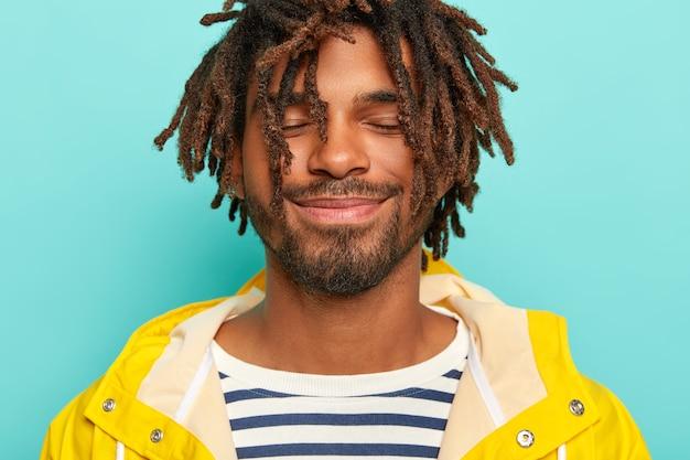 Uomo soddisfatto con la pelle scura, ha paura, indossa un impermeabile giallo e un maglione a righe, tiene gli occhi chiusi, immagina qualcosa di carino