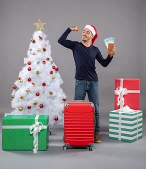 Uomo soddisfatto con la valigia rossa che tiene i suoi biglietti di viaggio e che mostra i muscoli del braccio su grigio