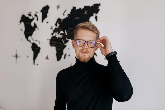 仕事で満足している人。オフィスの彼の職場でポーズをとりながらラップトップに取り組んで幸せな若い男。