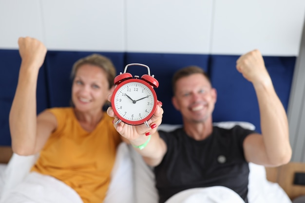 Satisfied man and woman lie in bed and hold alarm clock comfortable joint sleep concept