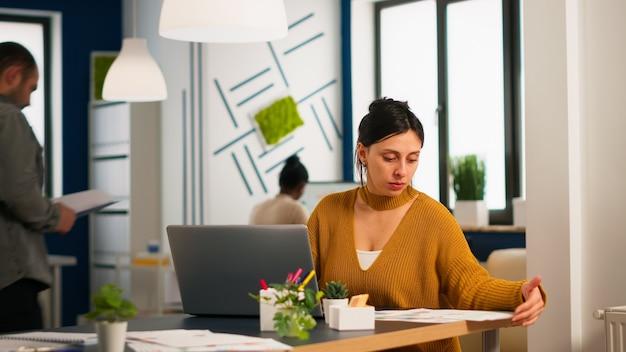 금융 스타트업 회사에서 일하는 책상에 앉아 노트북에 타이핑하는 재무 통계와 그래프를 확인하는 만족한 관리자. 다양한 팀이 현대 사무실에서 통계 데이터를 분석합니다.