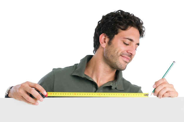Satisfied manual worker measuring with tape above a blank sign board ready for your text
