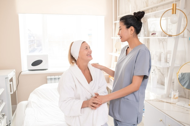 Satisfied mature beauty salon guest in robe sitting on procedure table and holding hand of asian cosmetologist while thanking her after procedure