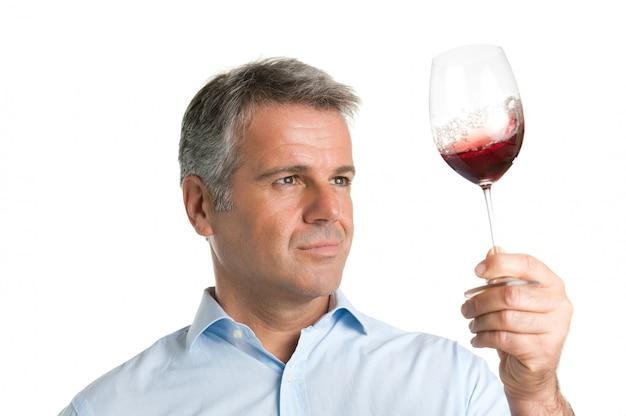 Довольный зрелый мужчина смотрит на бокал красного вина во время дегустации вин