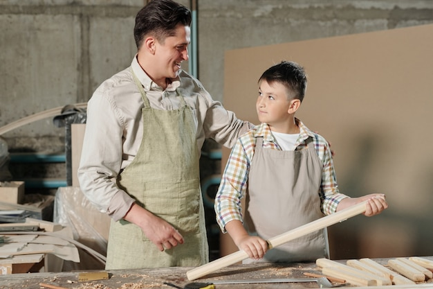 Satisfied middle-aged carpenter in apron being proud of teenage son praising him for good job in workshop