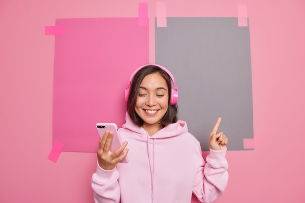 Satisfied millennial asian woman makes video call promots something indicates at blank space smiles pleasantly shows direction sale logo store banner wears hoodie poses against pink wall