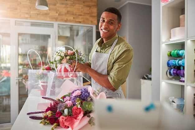 Satisfied mixed-race store manager working at the table with flowers and getting them inside a plastic package