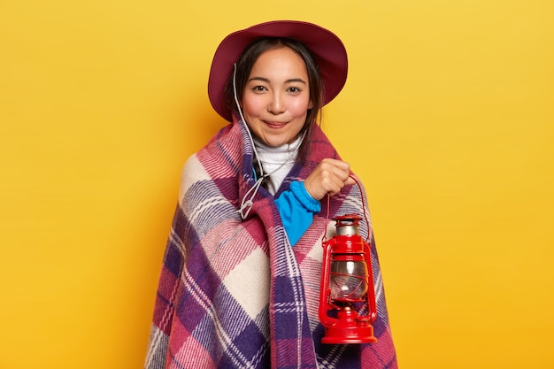 Satisfied mixed race woman feels cozy under soft checkered plaid, holds kerosene lamp for lightening, looks directly at camera, poses over yellow wall