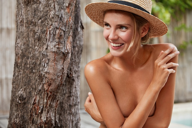 Satisfied naked woman hides breast, looks happily away, wears straw summer hats, has pleasant broad smile on face. nude female demonstrates well cared skin