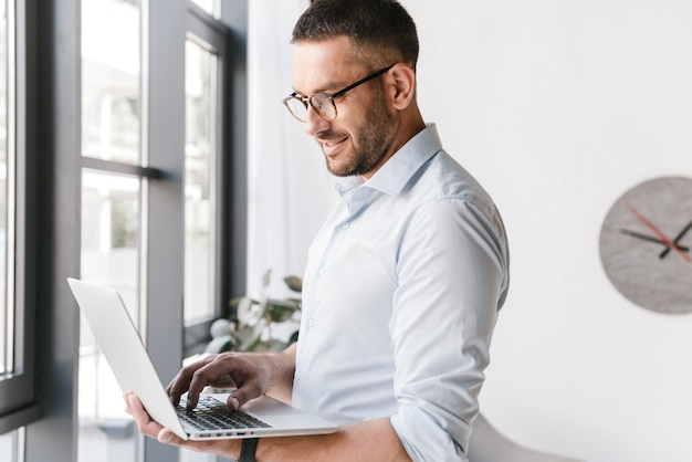 Довольный офисный мужчина в белой рубашке, выражающий успех, держа серебряный ноутбук во время работы в деловом интерьере
