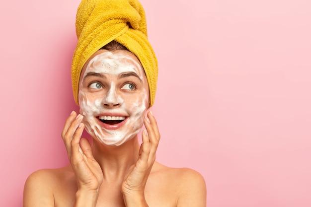 만족스럽고 유쾌한 여성은 얼굴에 거품 비누를 가지고 있고, 안색을 가꾸고, 먼지를 제거하고, 상쾌하고 행복해 보이며, 실내에서 알몸으로 서고, 머리에 노란색 포장 타월을 착용합니다.