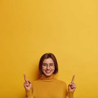 Satisfied pleased young woman promots product above, gives recommendation, stands with broad smile against yellow wall. take look there. european female turns your attention at banner.