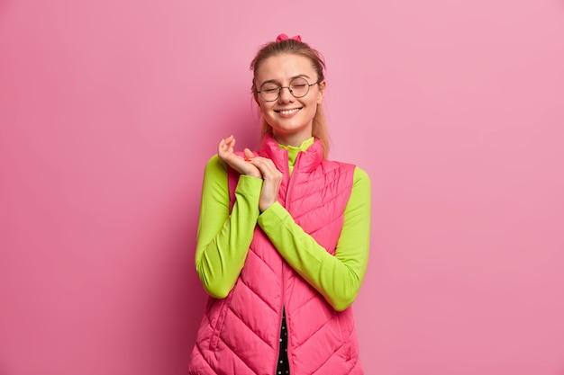 이빨 미소로 만족스러운 예쁜 유럽 소녀, 손을 문지르고, 눈을 감고, 긍정적 인 것을 기억하고, 둥근 안경을 쓰고, 분홍색 조끼를 입습니다.
