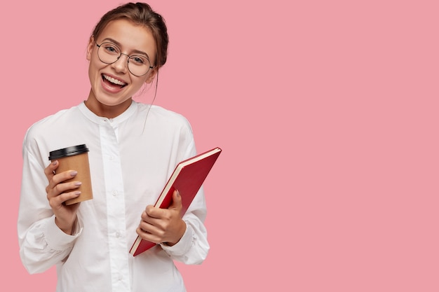 Satisfied pretty smiling young woman in spectacles, carries takeaway coffee