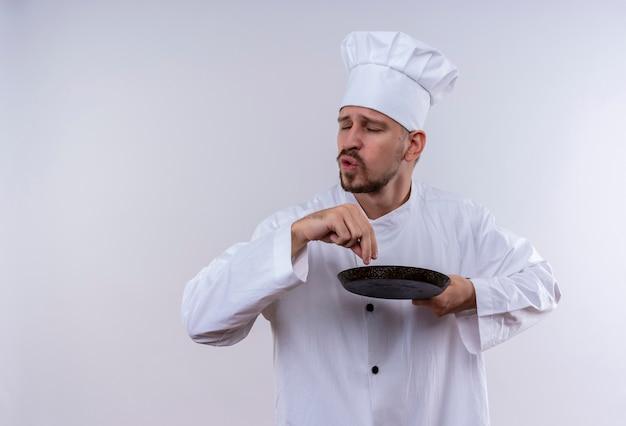 満足しているプロの男性シェフが白い制服を着て調理し、白い背景の上に立って身振りで示すパンを保持している帽子を調理します。