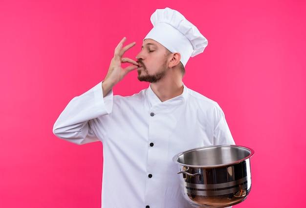 満足しているプロの男性シェフが白い制服を着て調理し、ピンクの背景の上に美味しい立っての兆しを見せているパンを保持している帽子を調理します。
