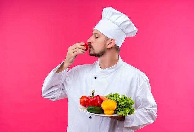 満足しているプロの男性シェフが白い制服を着て調理し、ピンクの背景の上に立ってトマトの香りを感じてプレートに新鮮な野菜を保持している帽子を調理します。